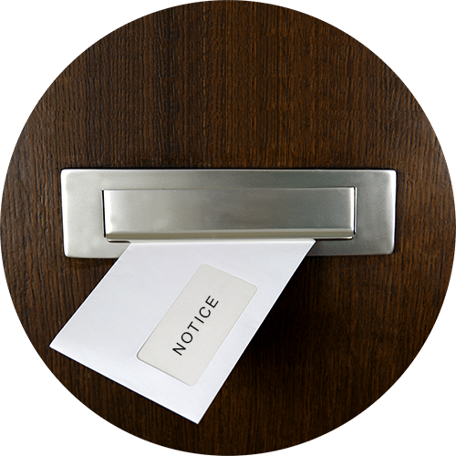 Round picture of a notice of debt collection going through a letter box